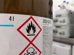 Label of a hazardous chemical in a scientific laboratory. Warning icons on flammability and toxicity.