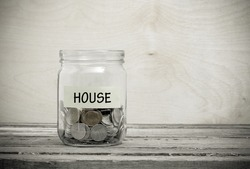 Label on a glass jar with the inscription - house. Glass jar with coins. Financial concept on wooden background