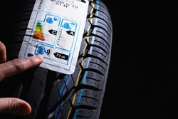 Label on tire with information about level of noise, braking distance on wet road, fuel efficiency. Finger shows on information sticker on tire.