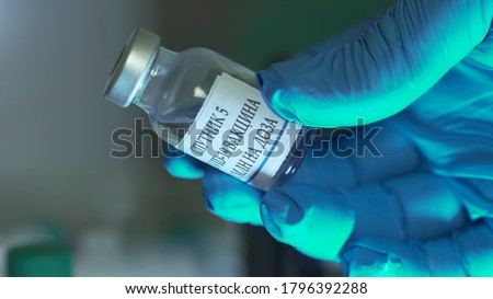 label translation: Sputnik 5, COVID-19 vaccine, 10ml per dose Gloved hand of a doctor holding a vial of Russian covid-19 vaccine or sputnik v