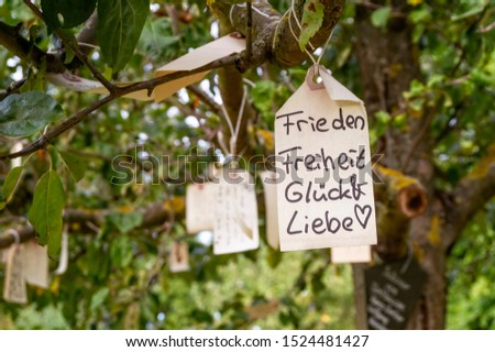 Label with the desire for peace, freedom, happiness and love hangs in a tree #1524481427