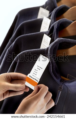 LABELING.  Clothing being labeled with a reduced price label in a store