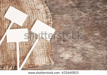 Labels-markers for plants lie on burlap, on a wooden brown background., Top view.