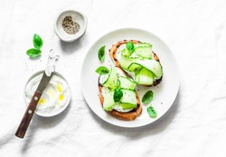 Labne and pickled cucumbers toast on a light background, top view. Sandwiches with soft cheese and cucumber - delicious healthy breakfast, snack. Flat lay