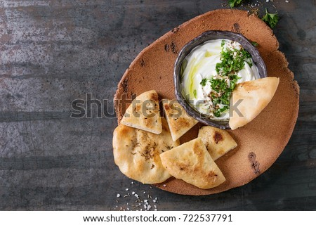 labneh middle eastern lebanese cream cheese dip with olive oil, salt, herbs served with traditional pita bread on terracotta plate over dark texture metal background. Top view with space Stockfoto ©