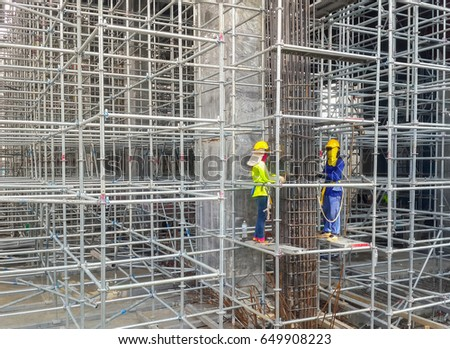Labor are tied to steel column of structure column. Metal girder extensive scaffolding providing platforms for stage structure support. #649908223