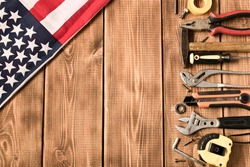 Labor day. American flag and various tools on a wooden background. The concept of labor day. Empty space for text