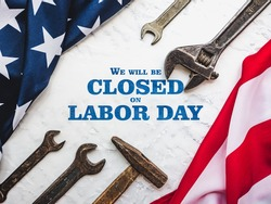 LABOR DAY. Hand tools and the Flag of the United States of America lying on the table. View from above, close-up. Congratulations to family, relatives, friends and colleagues. National holiday concept