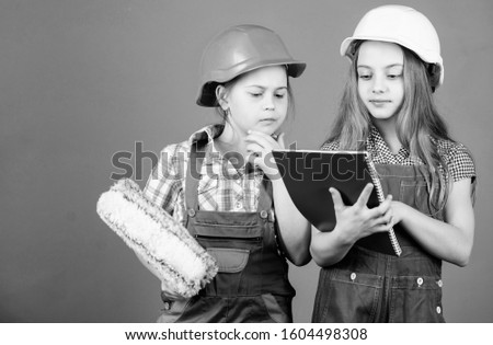 Labor day. 1 may. engineering idea. Foreman inspector. Repair. Little kids in helmet with tablet and roller. small girls repairing together in workshop. building inspector. professional inspector.