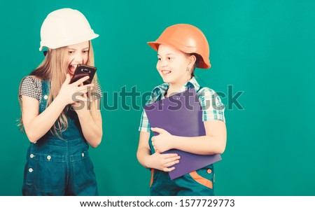 Labor day. 1 may. school project. Foreman inspector. Repair. Little kids in helmet with tablet. small girls repairing together in workshop. shouting on worker in phone call. discussing problems.