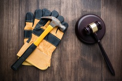 Labor law concept, wooden judge gavel and yellow construction gloves, construction and law concept