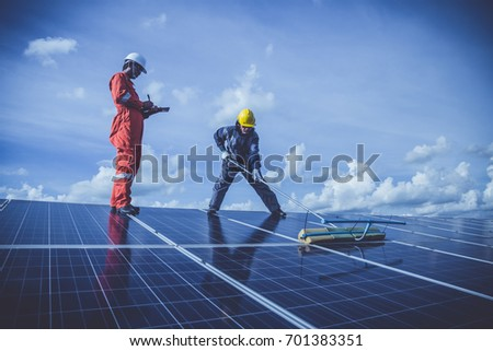 labor team working on cleaning solar panel with water clean at solar power plant
