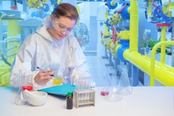Laboratory assistant at a chemical factory. Girl works in laboratory. Woman chemist near pipes. Laboratory assistant is writing something. Chemist takes samples at the factory. Scientific experiments
