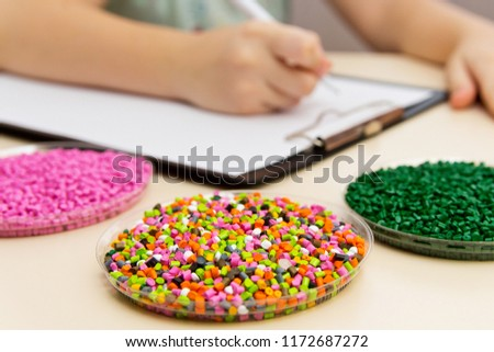 Laboratory assistant checks the quality of plastic pellets for industry. Plastic raw materials in granules . Polymer, a plastic resin. The dye in the granules of polypropylene and polyethylene.