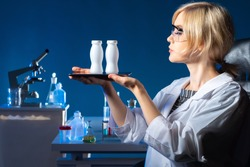 Laboratory assistant holds a smartphone and probiotics in his hands. Bottles with probiotic yogurt on phone screen. Woman advertising probiotic yogurt. Biologist examines beneficial microorganisms.