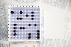 Laboratory battleship game made of spectrophotometer cuvette in a box, blank and filled in tables paper sheets around it