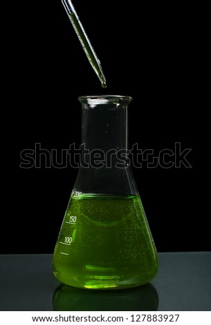 Laboratory beaker filled with green color liquid substances and laboratory pipette. Dark background