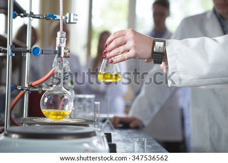 Laboratory equipment for distillation.Separating the component substances from liquid mixture.Pharmaceutical researcher holding Erlenmeyer flask demonstrating process in apparatus