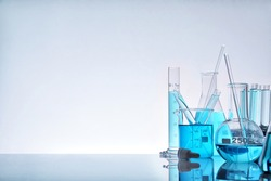Laboratory glass chemical containers full of blue liquid on glass table isolated. Horizontal composition. Front view