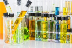 Laboratory glass chemical vials with colorful chemical solution and test tube with colorful chemical solution in a beaker, science background