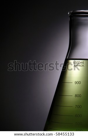 Laboratory glass conical Erlenmeyer flask filled with green liquid for an experiment in a science research lab