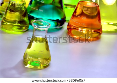 Laboratory glass conical Erlenmeyer flasks filled with assorted colors liquid for an experiment in a science research lab