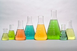 Laboratory glass conical Erlenmeyer flasks in a row filled with assorted colors liquid for an experiment in a science research lab