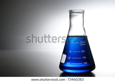 Laboratory glass Erlenmeyer conical flask filled with blue chemical liquid for a chemistry experiment in a science research lab