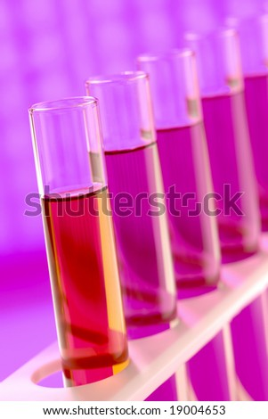 Laboratory glass test tubes filled with red liquid on a rack for an experiment in a science research lab