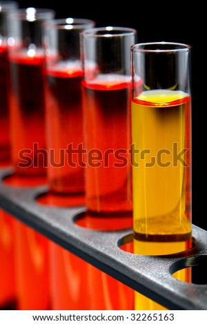 Laboratory glass test tubes filled with yellow and red liquid on a rack for an experiment in a science research lab