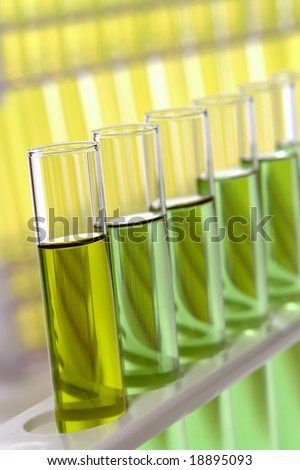 Laboratory glass test tubes filled with yellow liquid and green chemical solution on a rack for an experiment in a science research lab