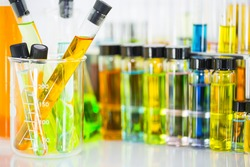 Laboratory glass test tubes with colorful chemical solution in a beaker test tubes and chemical vials and test tube with colorful chemical solution in test tubes rack as background, science background