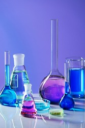 Laboratory Glass With Colorful Liquid. Close Up Of Laboratory Transparent Glassware With Multicolor Fluid On Table In Chemical Lab.