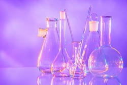 Laboratory glassware as a symbol of scientific activity. Laboratory glassware on a light background. Test tubes and different shapes stand side by side. Concept - manufacture of laboratory glassware.