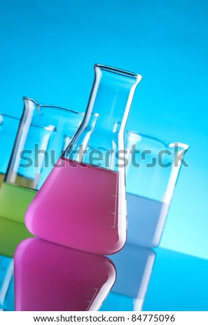 Laboratory Glassware - chemical flasks with colored solution. Focused on front flask with purple solution.