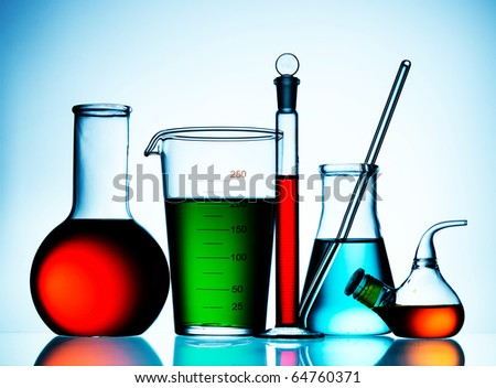 Laboratory glassware on blue background - stock photo