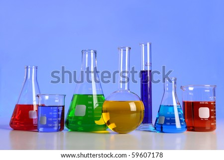 Laboratory glassware over blue background with reflections on table