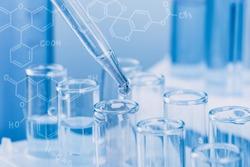 Laboratory glassware with a dropper dripping liquid into a test tube. scientific laboratory test tubes, laboratory equipment