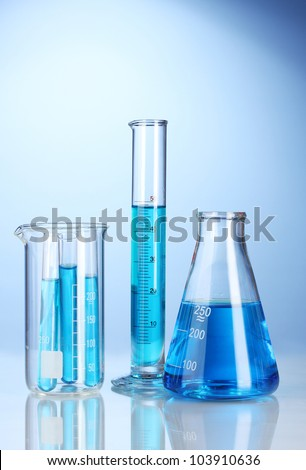 Laboratory glassware with blue liquid with reflection on blue background