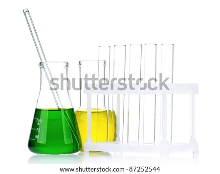 Laboratory glassware with colorful liquids and syringes on white background
