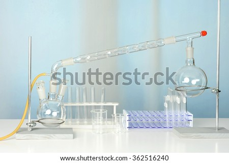 Laboratory glassware with distillation set on white table