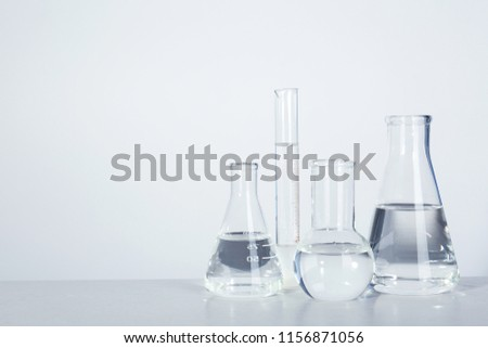 Laboratory glassware with liquid on table against light background. Chemical analysis