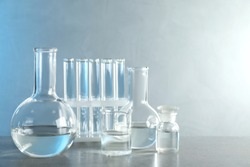 Laboratory glassware with liquid samples for analysis on grey table against toned blue background