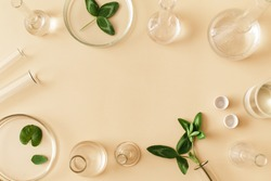Laboratory glassware with serum and oil on beige background. Natural medicine, cosmetic research, bio science, organic skin care products. Flat lay, top view, copy space.