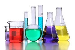 Laboratory glassware with various colored liquids with reflection on table