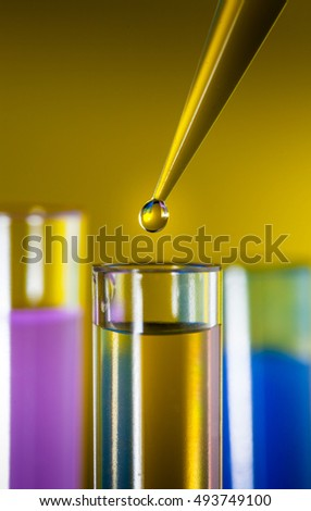 Laboratory pipette with a drop of substance over test tubes on clorful background