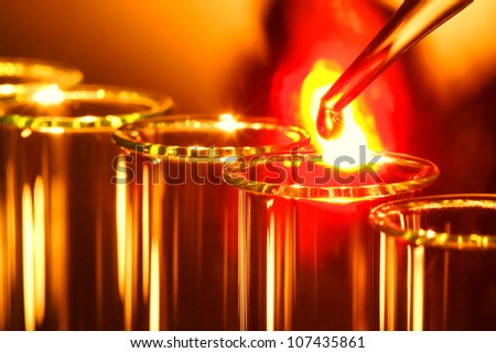 Laboratory pipette with drop of burning hot melting liquid with intense fire ball explosion over glass test tubes for a scientific experiment in a science research lab