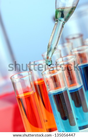 Laboratory pipette with drop of color liquid over glass test tubes, close up
