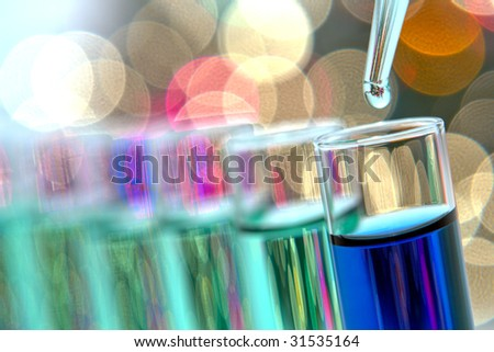 Laboratory pipette with drop of green liquid over glass test tubes filled with blue chemical solution for an experiment in a science research lab