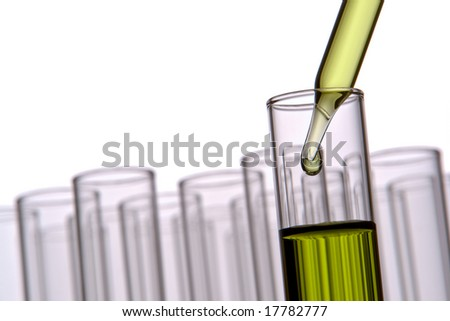 Laboratory pipette with drop of green liquid over test tubes for an experiment in a science research lab